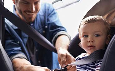 En pappa sätter fast sitt barn i bilbarnstol